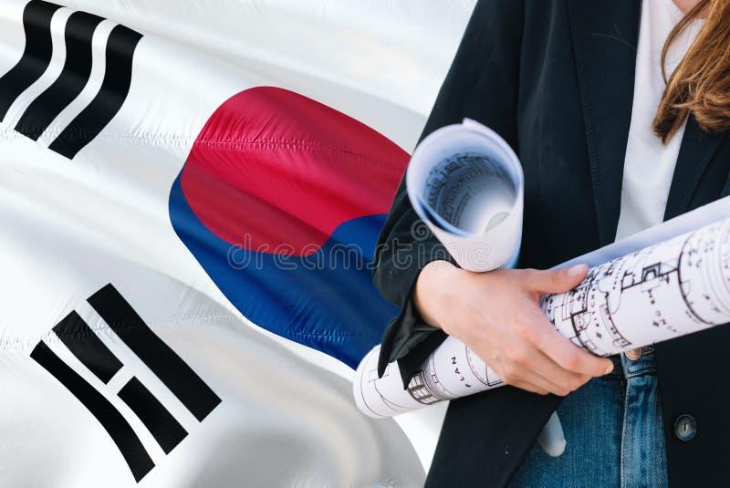 Poludniowo-koreański architekta kobiety mienia projekt przeciw korei południowej falowania flagi tłu Budowy i architektury poj?ci zdjęcia royalty free