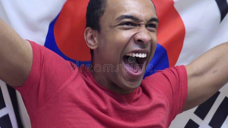 Poludniowo-koreański fan świętuje trzymający flaga Południowy Korea w zwolnionym tempie fotografia royalty free