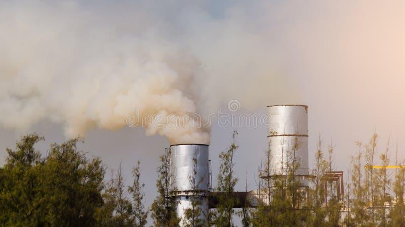 Poluição do ar atmosférica de industrial com árvore verde fotografia de stock