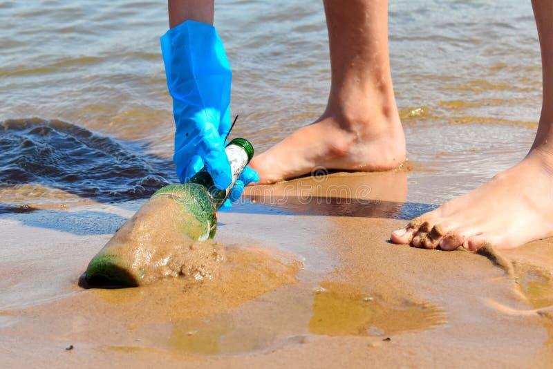 Poluição dos rios e do oceano Problema da polui??o ambiental Os voluntários limpam a praia do lixo Garrafa de vidro dentro foto de stock royalty free