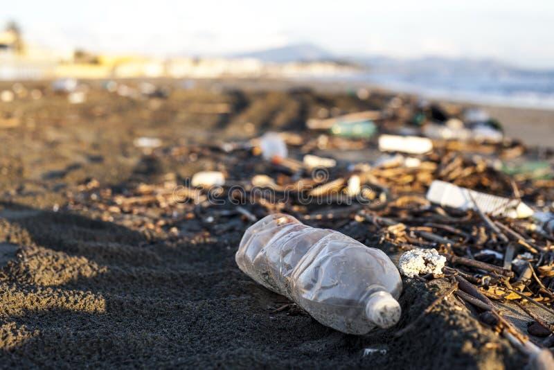 Poluição - garrafa de água plástica em uma praia foto de stock royalty free