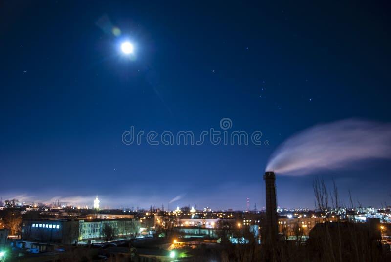 Polui??o do ar pelo fumo Arquitetura da cidade da noite no luar fotos de stock royalty free