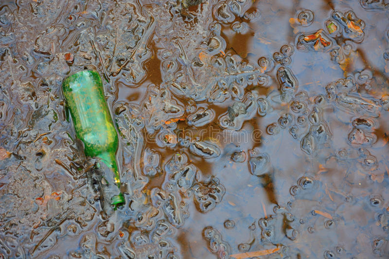 Polution environement, old green bottle in a mud poel. Polution environement,detail of old green bottle in a mud water flaque stock images