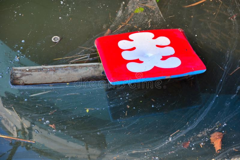 Polution, red symbol on a stick in dirty water. But if you look well on the right side of the image you see fish everywhere royalty free stock photo