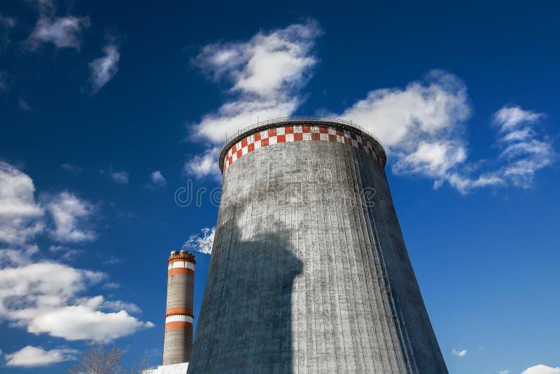 Polution, smoking pipes against blue sky. One huge and one tall pipes. polution, smoking pipes against blue sky stock photos