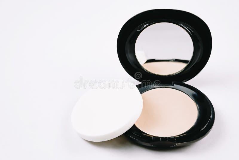 Polvere compatta cosmetica di trucco del fronte nella custodia in plastica rotonda nera con lo specchio e spugna isolata su fondo immagini stock