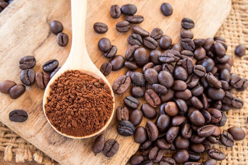 Polvere del caffè in chicchi di legno di caffè e del cucchiaio sulla tavola di legno immagini stock