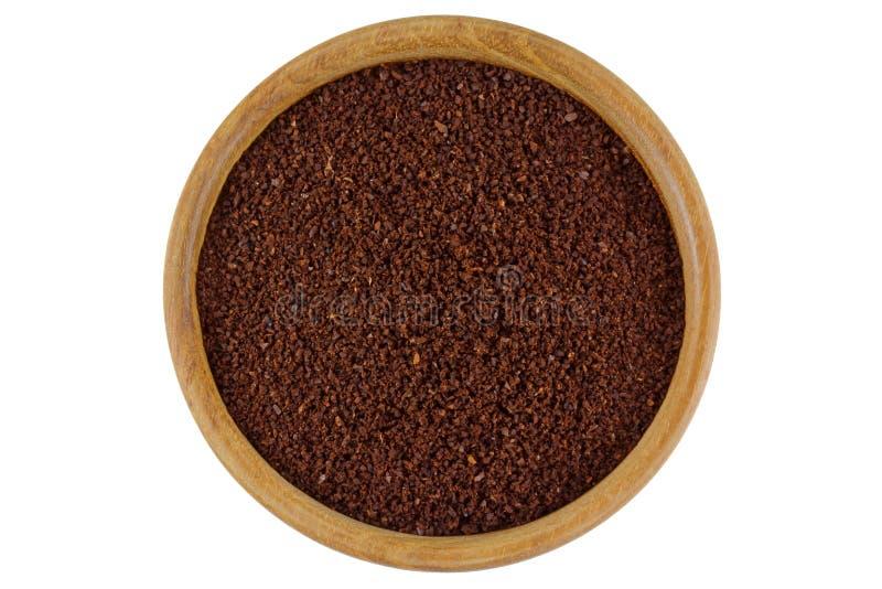 Polvere del caffè macinato in una ciotola di legno isolata sul backgrou bianco fotografia stock
