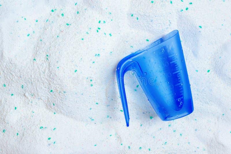 Polvere del detersivo di lavanderia di lavaggio e tazza di misurazione di plastica blu immagine stock