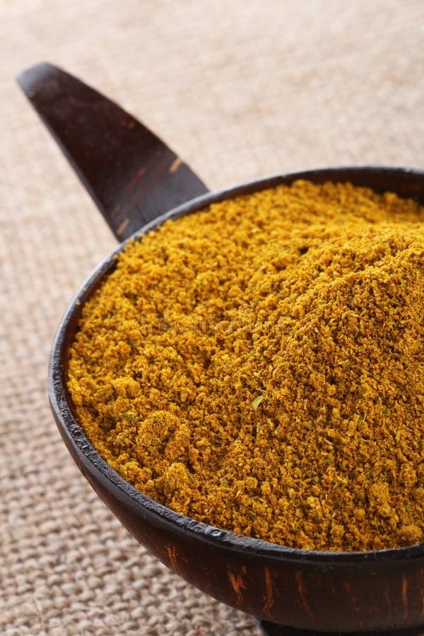 Polvere di curry di Madras nella priorità bassa della tela di iuta della ciotola fotografia stock libera da diritti