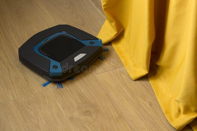 Polvere di pulizia dell'aspirapolvere del robot su un pavimento lungo le tende immagini stock