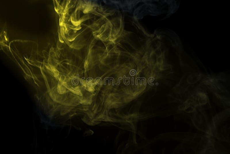 Polvere o fumo dorata astratta isolato su fondo nero fotografia stock