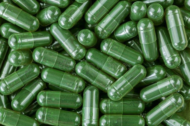 Polvere verde di Spirulina, cianobatteri in chiare capsule fotografie stock