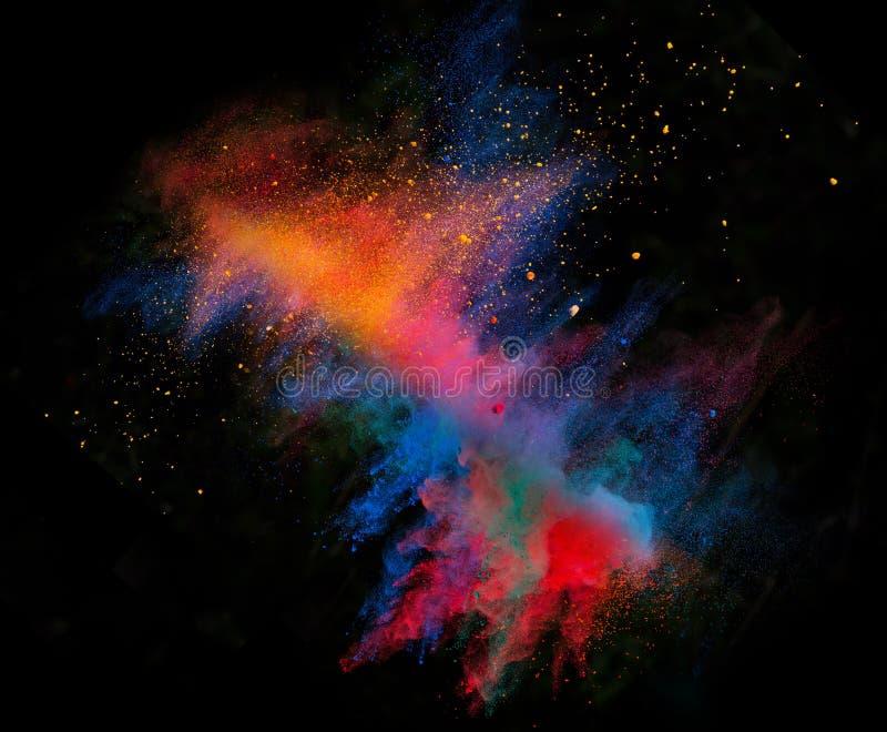 Polvo colorido lanzado en fondo negro imagen de archivo libre de regalías