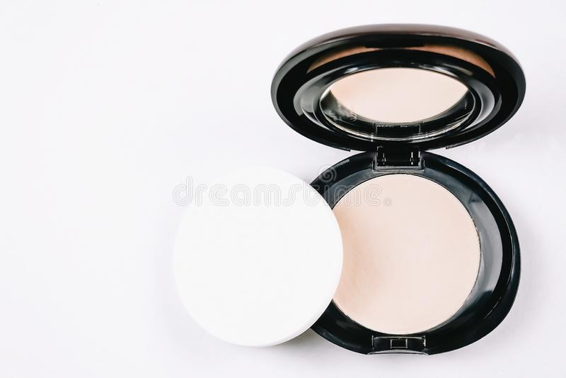 Polvo compacto cosmético del maquillaje de la cara en estuche de plástico redondo negro con el espejo y esponja aislada en el fon imagen de archivo