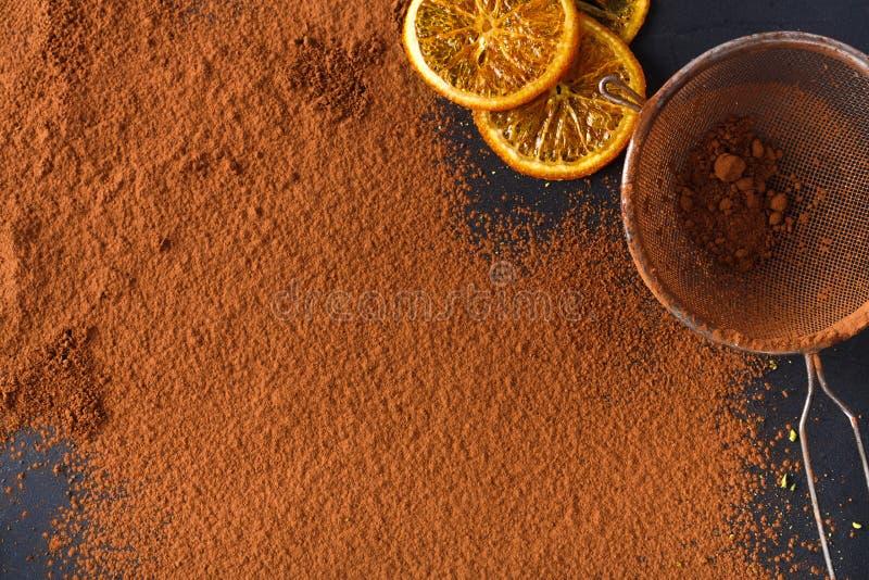 Polvo de cacao en un tamiz sobre fondo negro de la pizarra fotos de archivo