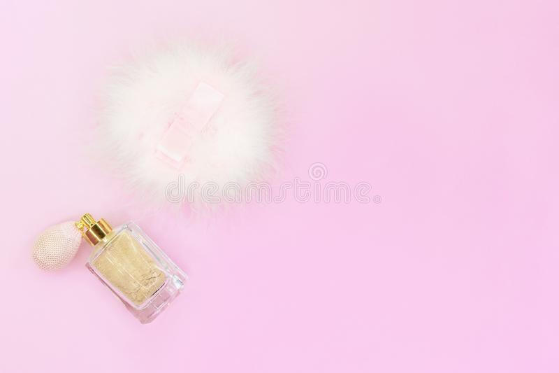 Polvo de cara flojo del brillo beige de oro con la esponja del rociador y del soplo en fondo rosado imagen de archivo