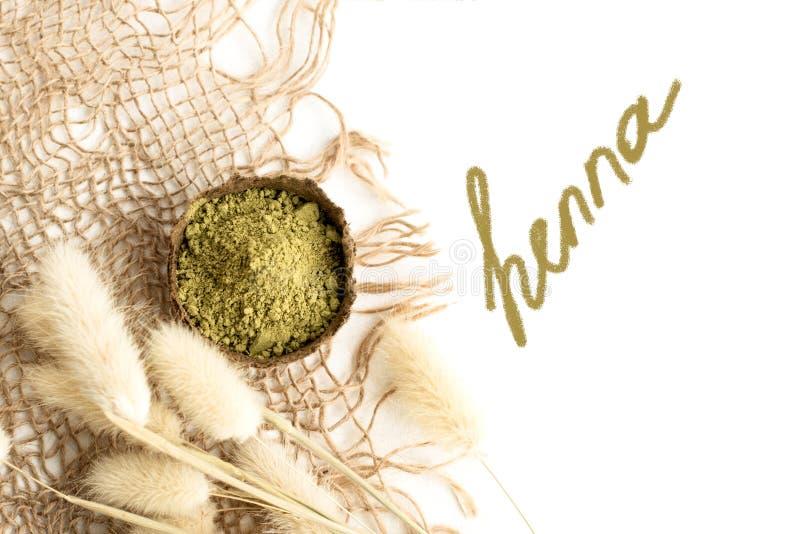 Polvo de la alhe?a para el mehendi de te?ido del pelo y de las cejas y del dibujo en las manos, con la hoja de palma verde imagenes de archivo