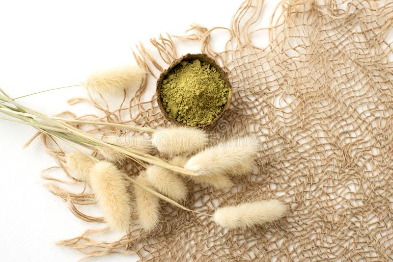Polvo de la alhe?a para el mehendi de te?ido del pelo y de las cejas y del dibujo en las manos, con la hoja de palma verde foto de archivo libre de regalías