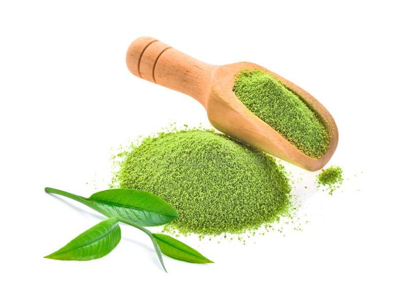 Polvo de la hoja de té fresca y del té verde en la cucharada de madera aislada encendido foto de archivo