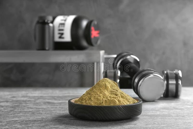 Polvo de la proteína del cáñamo en cuenco y pesas de gimnasia en la tabla foto de archivo
