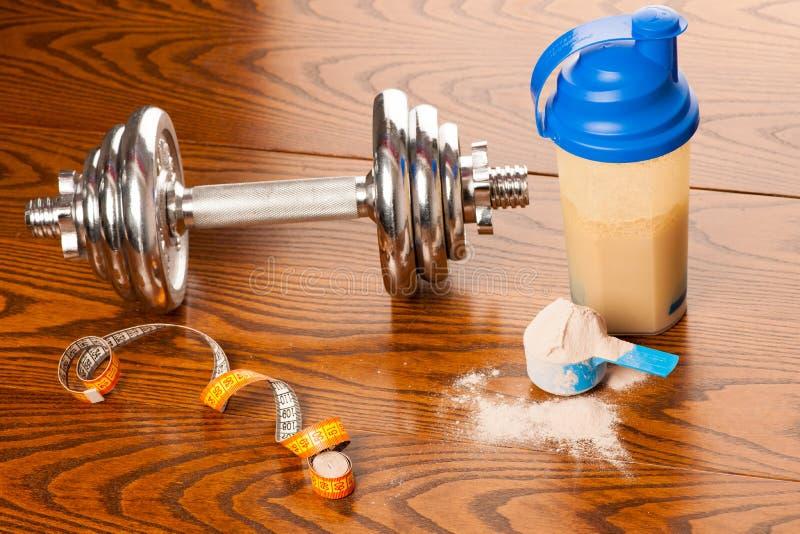 Polvo de la proteína en la cucharada, la pesa de gimnasia, la cinta y el plástico s del metro foto de archivo libre de regalías