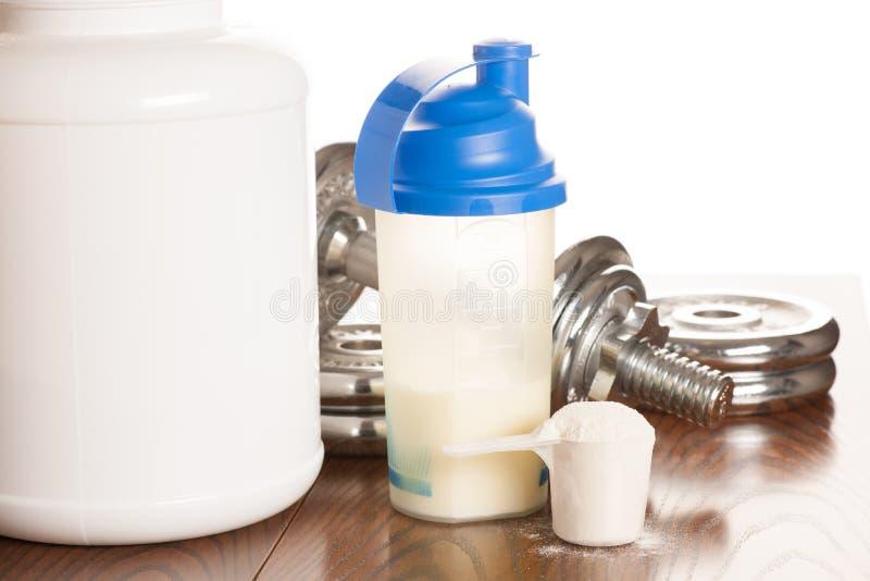 Polvo de la proteína en scoope con pesas de gimnasia en el fondo - suero foto de archivo libre de regalías
