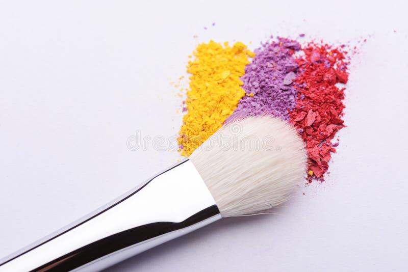 Polvo de la sombra de ojos y cepillo desmenuzados coloridos del maquillaje en un fondo blanco foto de archivo libre de regalías