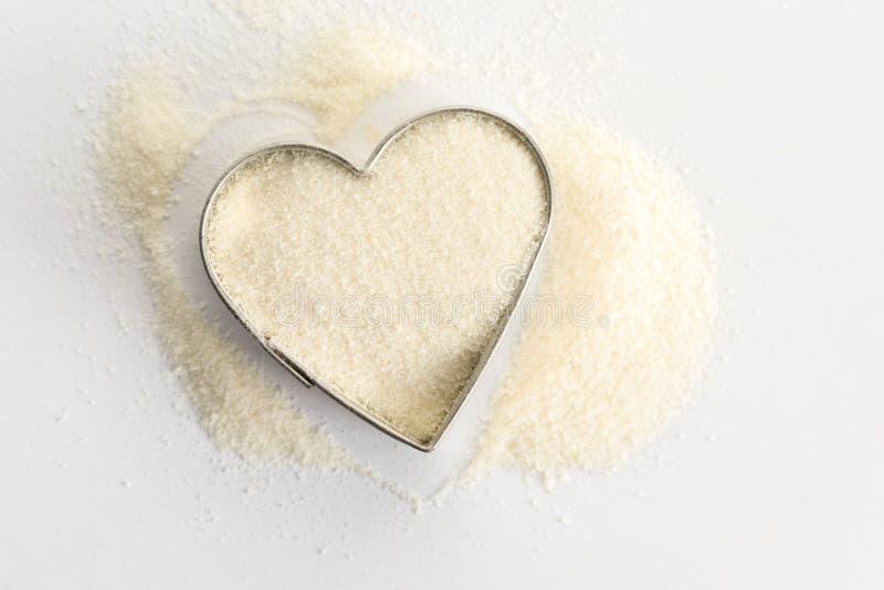 Polvo del colágeno en una forma del corazón foto de archivo libre de regalías