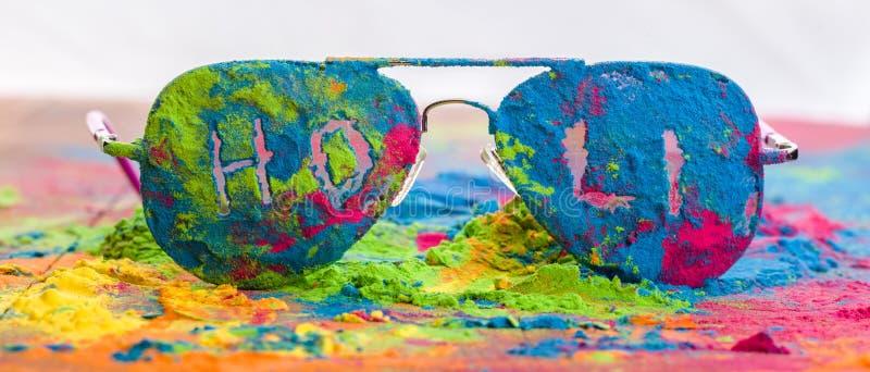 Polvo del color de Holi en las gafas de sol Colores orgánicos de Gulal en las lentes para el festival de Holi, tradición hindú fe fotos de archivo