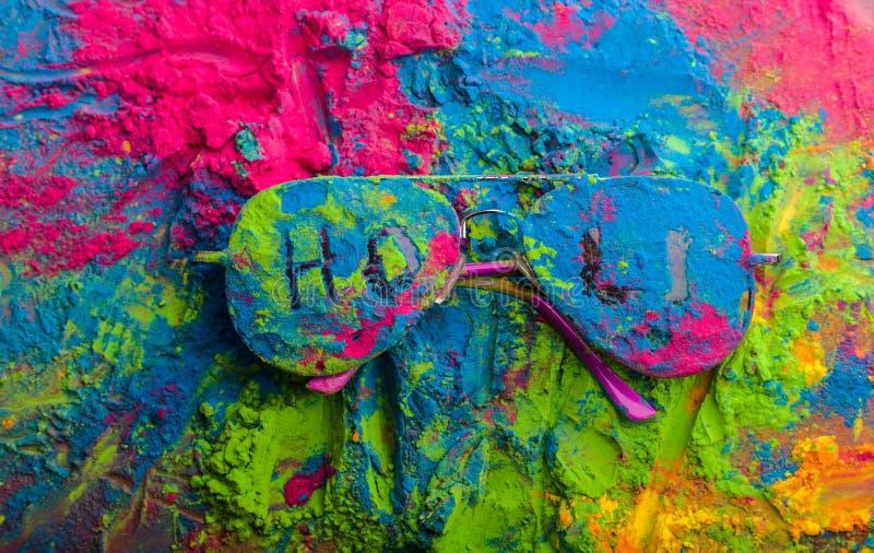 Polvo del color de Holi en las gafas de sol Colores orgánicos de Gulal en las lentes para el festival de Holi, tradición hindú fe imágenes de archivo libres de regalías