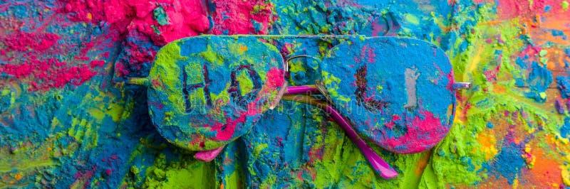 Polvo del color de Holi en las gafas de sol Colores orgánicos de Gulal en las lentes para el festival de Holi, tradición hindú fe foto de archivo libre de regalías