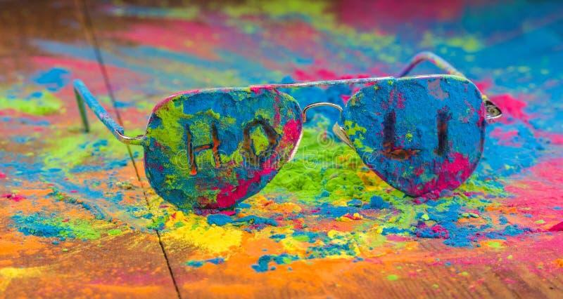 Polvo del color de Holi en las gafas de sol Colores orgánicos de Gulal en las lentes para el festival de Holi, tradición hindú fe imagen de archivo