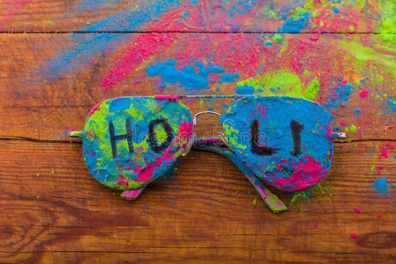 Polvo del color de Holi en las gafas de sol Colores orgánicos de Gulal en las lentes para el festival de Holi, tradición hindú fe fotografía de archivo