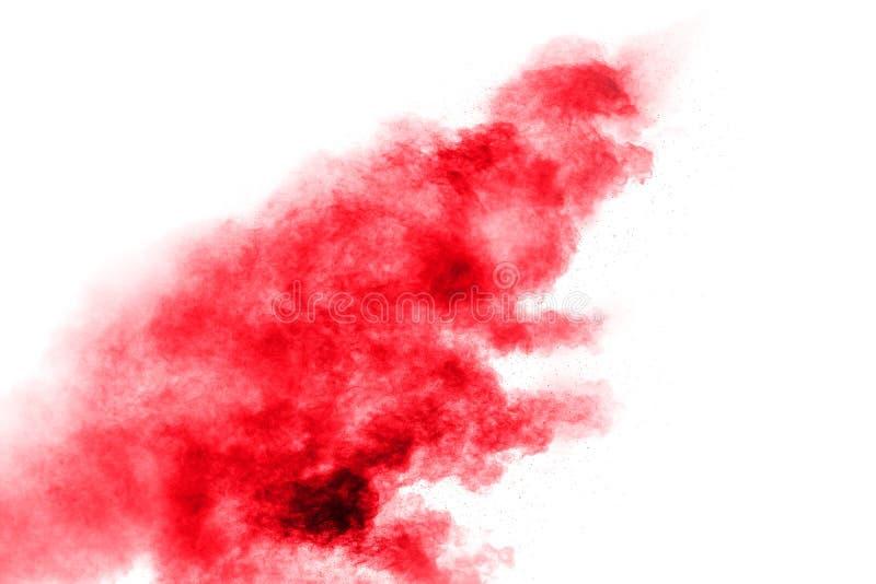 Polvo rojo abstracto salpicado en el fondo blanco Explosi?n roja del polvo Movimiento del helada de salpicar rojo de las part?cul foto de archivo
