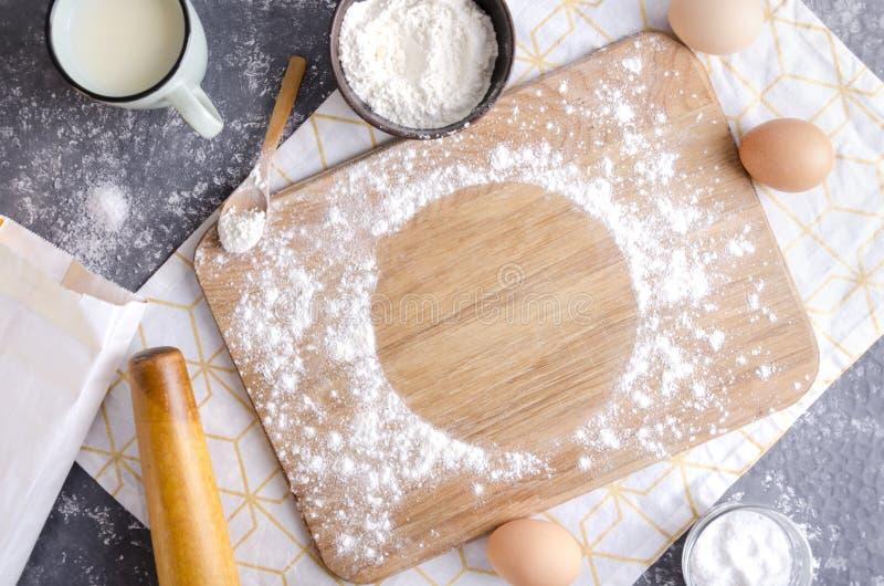 Polvoreda de madera de la tabla de cortar con la harina para la pasta Punto redondo vacío para el texto en la tabla de cortar Tab fotos de archivo