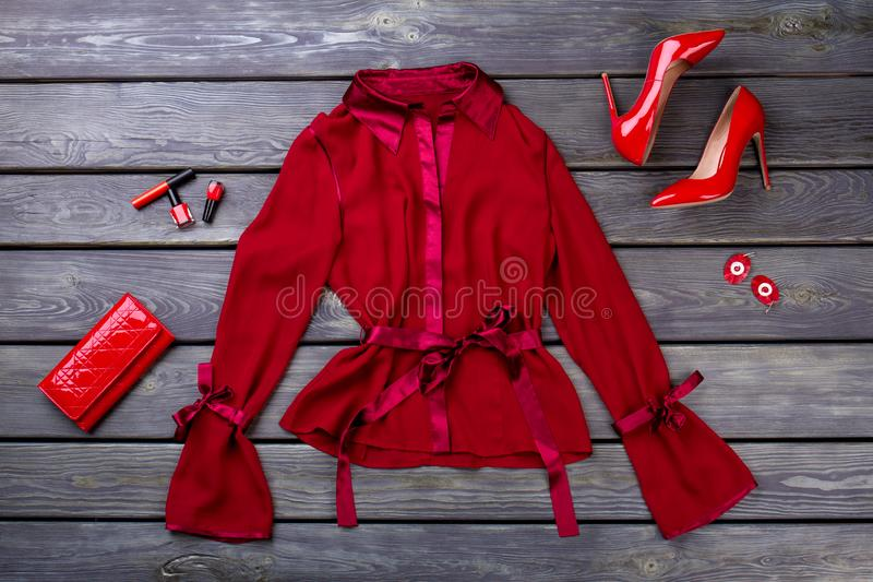 Polyester satin lycra fabric red jacket. Glamour fancy clothing and accessories. Flat lay, grey wooden surface background stock photo