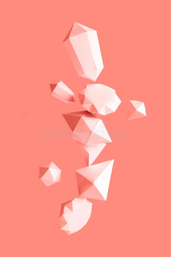 Polygonal diamonds made of paper on a blue background. Jewelry concept. Levitation Toned trendy coral stock photography