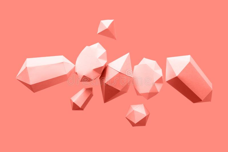 Polygonal diamonds made of paper on a blue background. Jewelry concept. Levitation Toned trendy coral royalty free stock photos