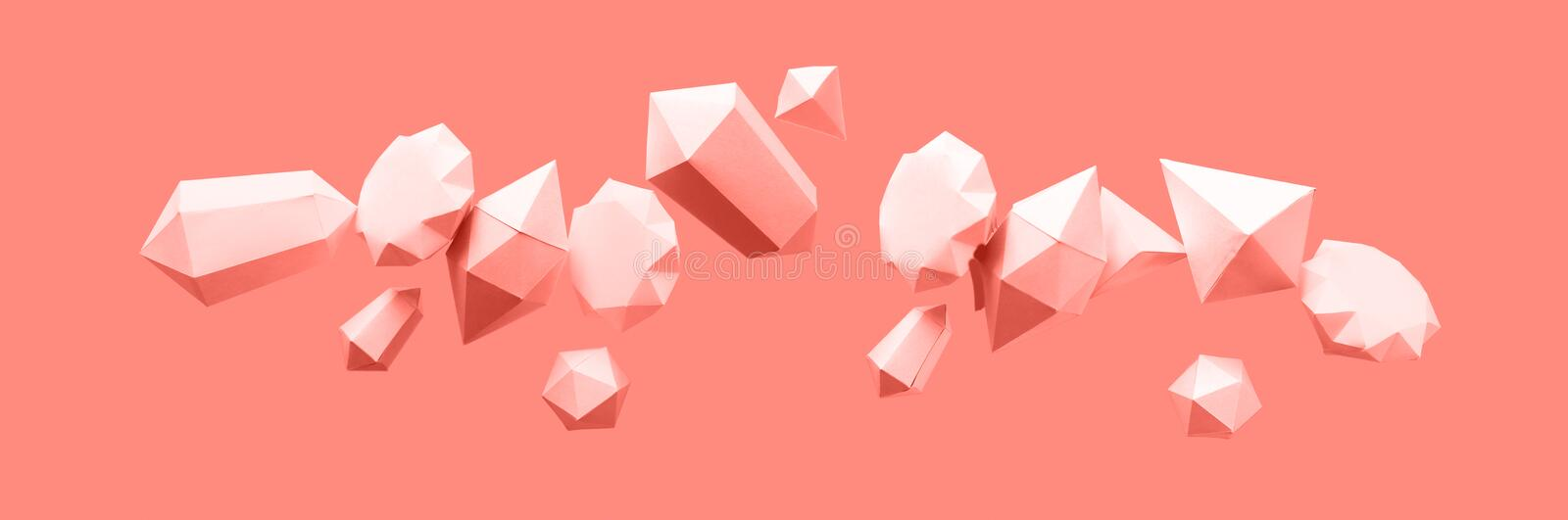 Polygonal diamonds made of paper on a blue background. Jewelry concept. Levitation Toned trendy coral stock image