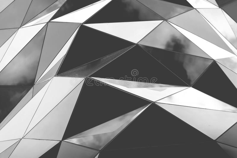 Polygonal triangle glass facade. Of modern building. Cloudy sky reflects in glass stock images