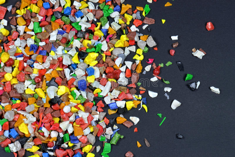 Polymer regrind. Different dyed polymer regrind after milled in a shredder for recycling process stock photos