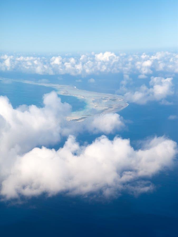 polynesia O anel do atoll no oceano é visível através das nuvens Silhueta do homem de negócio Cowering imagens de stock