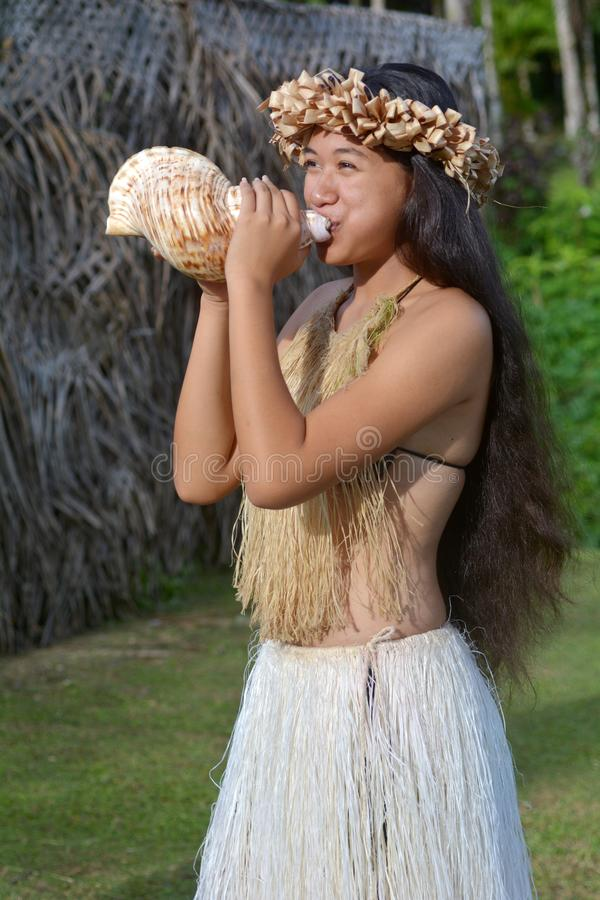 Polynesian Cook Islander woman blowing conch shell in Rarotonga stock photos
