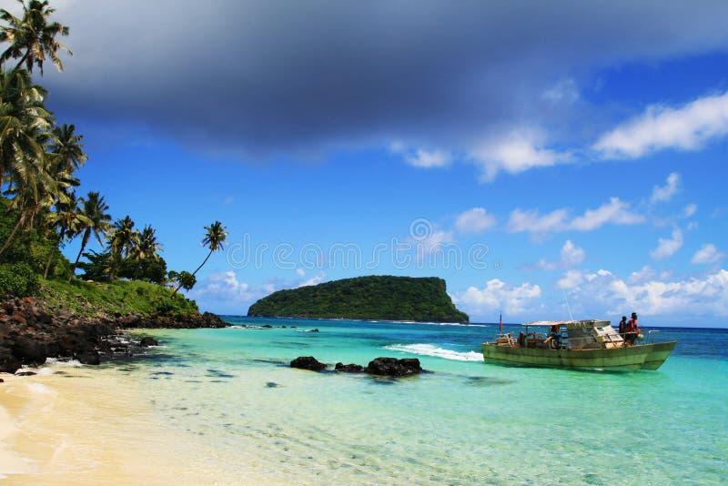 Polynesian fiskare på fartyget, sandiga tropiska Stilla havetstrandSamoa öar royaltyfri bild