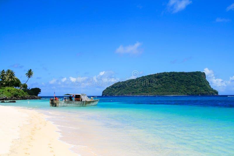 Polynesian fiskarefartygskeppsdocka på den vita guld- sandiga Lalomanu stranden på det tropiska paradiset i den Stilla havetUpolu fotografering för bildbyråer