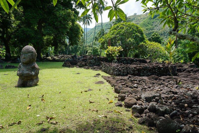 Polynesian gammal stenstruktur och staty Tahiti arkivbilder