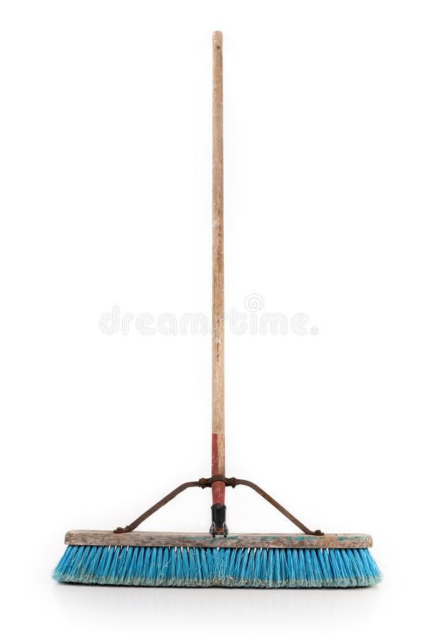 Polypropylene Push Broom. Dirty polypropylene push broom resting on a wall isolated on white stock photos