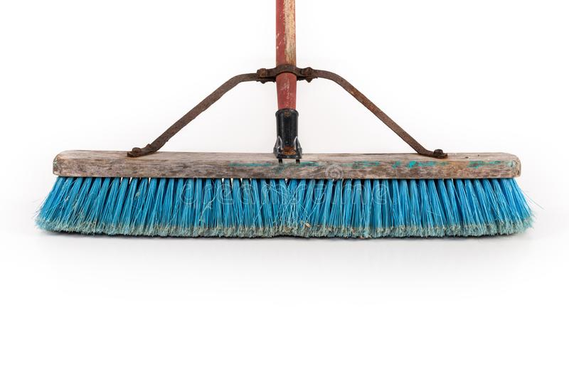Polypropylene Push Broom. Dirty polypropylene push broom resting on a wall isolated on white stock photography
