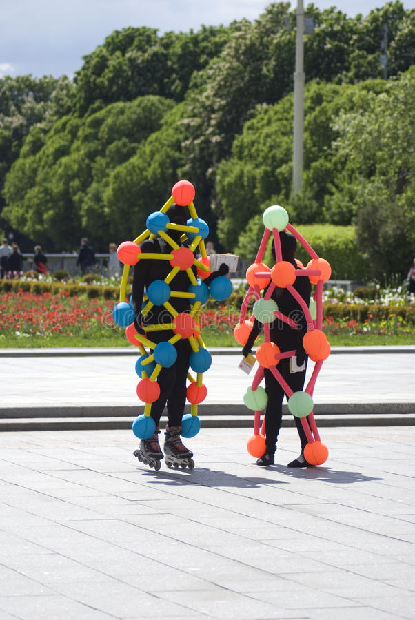 Polytech Festival in Gorky park, Moscow. Actors pose for photos. MOSCOW - MAY 25, 2017: Actors dressed in black costumes decorated by colorful red, orange, blue royalty free stock image